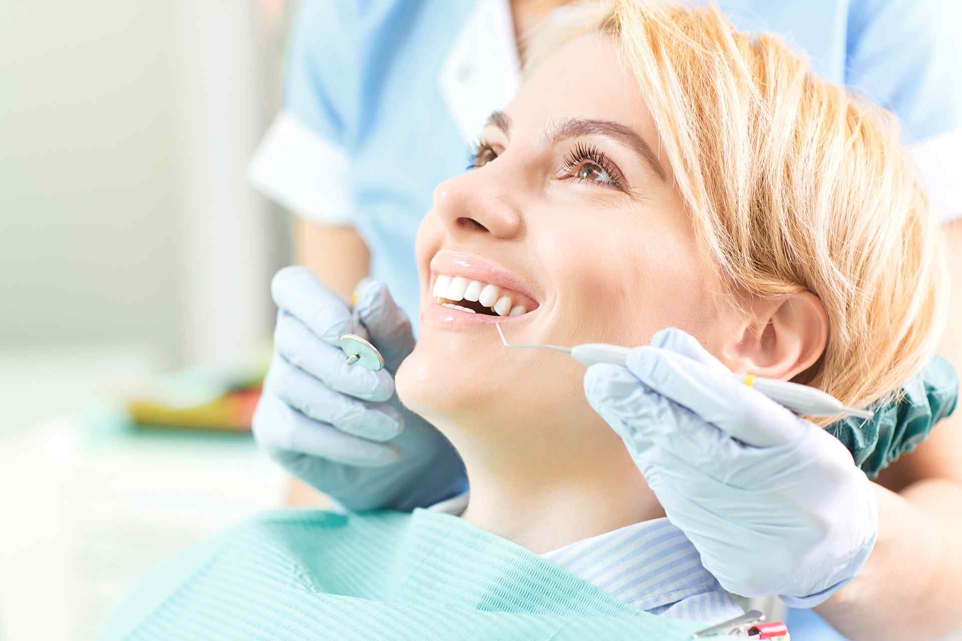 Woman smiling during a teeth cleaning