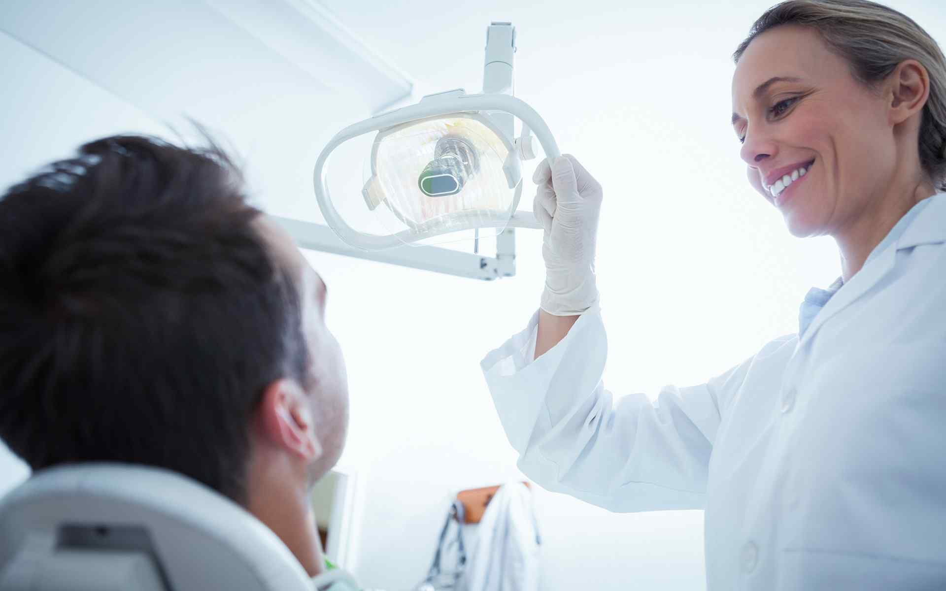 Dental hygienist adjusting dental lamp